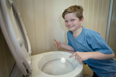 Boy covering a toilet with plastic as a prank
