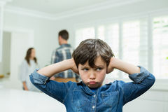 Boy covers his ears with his hands while parents arguing in background Royalty Free Stock Photos