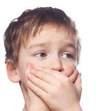Boy covers mouth with his hands. Stock Images