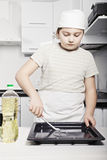 Boy covers pan with oil Stock Image