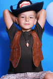 The boy cowboy. On a blue background Royalty Free Stock Images
