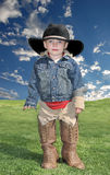 Boy in Cowboy Hat and Boots. Cute little boy in black cowboy hat and brown boots standing on meadow Royalty Free Stock Photography