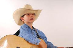 Boy with cowboy hat and guitar. Portrait of young boy in cowboy hat with acoustic guitar, studio background Stock Photography