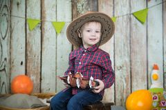 The boy in the cowboy hat. Boy in a cowboy hat holding a toy ship royalty free stock photos