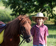 Boy with cowboy hat and horse Stock Images