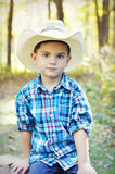 Boy with Cowboy Hat. Portrait of a young five year old boy with a cowboy hat and blue, white and red plaid shirt in front of an autumn forest. He has a very stock image