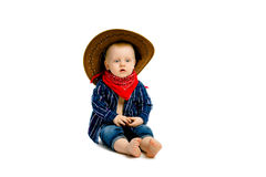 Boy in a cowboy hat sitting on a white floor Royalty Free Stock Image