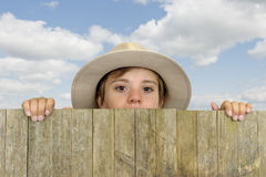 Boy with cowboy head looking above a wooden gate Royalty Free Stock Photos