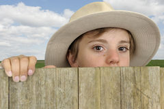 Boy with cowboy head looking above a wooden gate Stock Photos