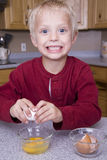 Boy cracking eggs in bowl Royalty Free Stock Photography
