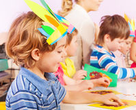Boy in crafting kindergarten class. Boy in handmade headwear gluing paper to cardboard in class with nurse and kids on background stock image