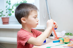 Boy crafting with paper sitting on table, early brain developing Stock Images