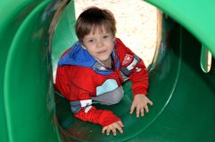 Boy crawling through a playground tunnel stock images