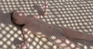 Kid crawling on warm sand under the net shed stock video footage