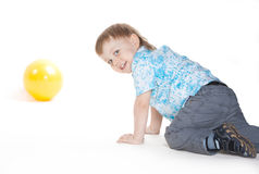 Boy crawling on white background. Boy crawling to yellow toy balloon on white background royalty free stock photos