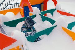 Boy crawls in snowdrifts on the Playground. He plays in a wooden maze. royalty free stock photo