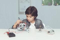 The boy creates a robot. He measures his data with a multimeter. The boy observes the measurements Stock Images