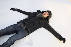 Boy creating snow angels Stock Photos