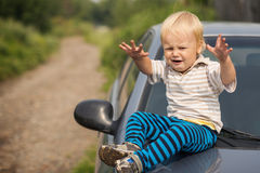 Boy Cries By the Car. Little Boy Sit on the Car Royalty Free Stock Images