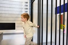 Boy criminal escapes from prison, police station on playground. Little boy criminal escapes from prison, police station on playground Royalty Free Stock Photo