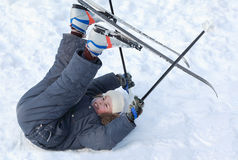 Boy with cross-country skis lying on snow Stock Photos