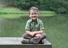 Boy cross-legged on a bench at pond Royalty Free Stock Photos
