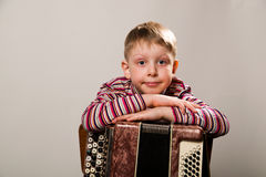 The boy crossed his arms and leaned on the accordion Royalty Free Stock Photography