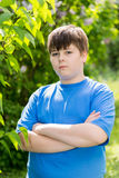 The boy crossed his arms in summer park Stock Photos