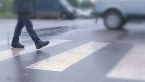 Boy crosses the road at a pedestrian crossing in the rain. Legs close-up. Boy crosses the road at a pedestrian crossing in the rain. Legs close-up stock video footage