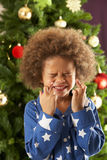 Boy Crossing Fingers In Front Of Christmas Tree Royalty Free Stock Images