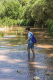 Boy crossing a river Stock Photography