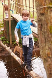 Boy Crossing Stream Balancing On Log At Activity Centre Stock Images