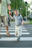 Boy crossing the street at a crosswalk. Little boy holding father's hand crossing the street at a crosswalk on a green traffic light Royalty Free Stock Photography