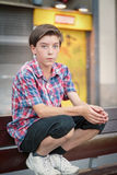 Boy crouching on a bench Stock Photography