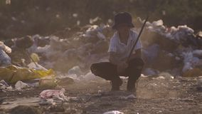 Boy crouching in dump. Medium shot of boy crouching and making dust by stick in dump stock photos