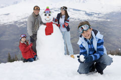 Boy (7-9) crouching in snow, family by snowman in background, smiling, portrait Royalty Free Stock Photography