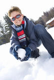 Boy (7-9) crouching in snow field, holding snowball, smiling, portrait Royalty Free Stock Photo