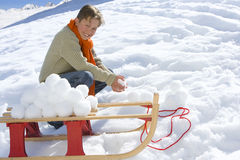 Boy (7-9) crouching in snow by sled and snowballs, smiling, portrait Royalty Free Stock Image
