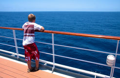 Boy on a cruise. Young boy on vacation looking over the railing of a cruise liner at bright blue sea in sunshine Stock Image