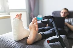 Boy with crutches and broken leg at home. Boy with crutches and broken leg grounded at home stock images