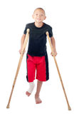 Boy with crutches. An injured boy with leg cast smiles bravely Stock Photos