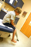 A Boy With Crutches Sits, Awaiting The Doctor Stock Photos