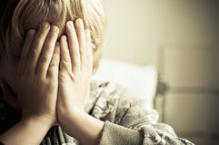 Boy crying. A boy holds his head in his hand crying Stock Images