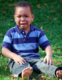 Boy Crying. A young boy sits outside on the grass upset and crying Stock Photo