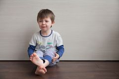 The boy is crying. The child is sitting on the floor. stock image