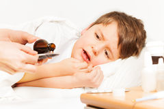 Boy crying while mother pouring coughing syrup. Sick kid boy laying in bed and crying while mother pouring coughing syrup from bottle with copy-space to metering Stock Image
