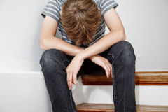 Boy crying while sitting on the stairs stock photo