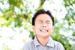 Boy crying and tears. Young Asian boy sad and crying in the garden in summer with tree and bokeh Stock Photography