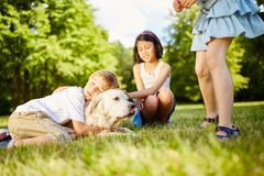 Boy cuddles with Golden Retriever. In the park and hugs him royalty free stock images