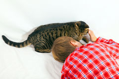 Boy cuddles his tabby cat Royalty Free Stock Photos
